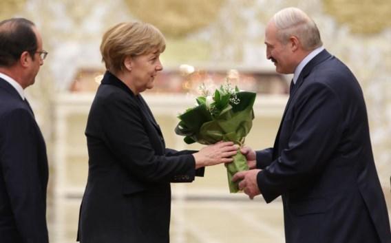 De Wit-Russische president Loekasjenko bedacht Angela Merkel met een bos witte bloemen. Zij twijfelde tussen een te strenge en een te vriendelijke blik.