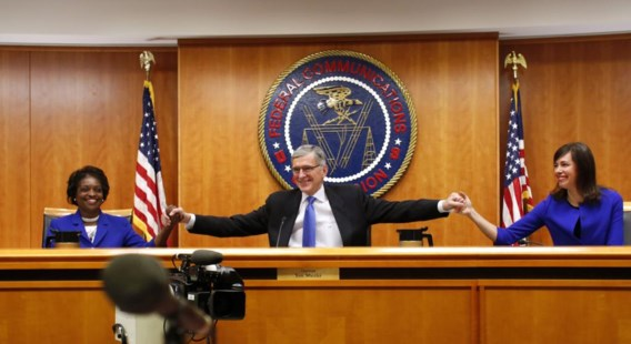 Voorzitter Tom Wheeler van de Federal Communications Commission begroet twee commissieleden aan het begin van de zitting over netneutraliteit.