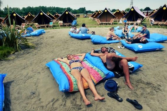 """<p>Ze zijn net zo uitgeput als de andere bezoekers, maar dankzij het comfortabele kussen kunnen deze jongeren twee vliegen in één klap slaan: hun roes uitslapen, en genieten van de zon. <span class=""""credit"""">Koen Bauters</span></p>"""