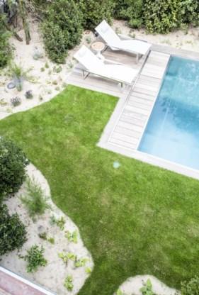 Het strakke zwembad in inox werd naadloos geïntegreerd in de organische omgeving.