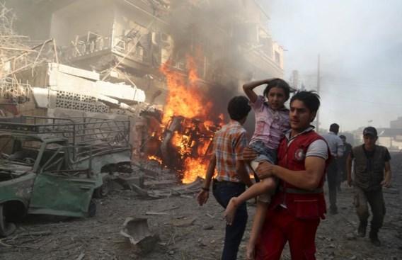 Een medewerker van het Rode Kruis draagt een meisje weg na een bombardement in Douma, nabij Damascus.