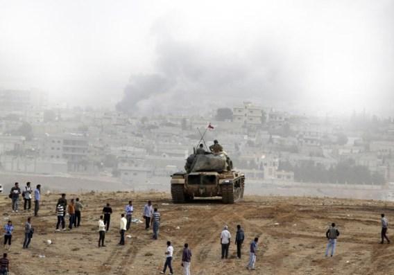 Turkse soldaten kijken vanop hun tank neer op de Syrische stad Kobani, nabij de Turkse grens.