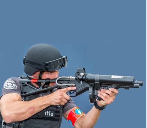 Een lid van het Snelle Respons Team demonstreert een 'less lethal' wapen dat kunststof projectielen afvuurt.