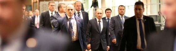 De Russische president Vladimir Poetin met zijn (veiligheids)entourage, maandag in het VN-gebouw in New York, zelfverzekerd op weg naar het spreekgestoelte.