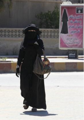 Een gesluierde vrouw in de straten van Raqqa doet wat de kledijvoorschriften van ISIS haar op het publiciteitsbord dicteren.