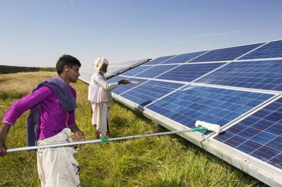 Werknemers halen het stof van een zonnepanelenpark in India, om zo de effeciëntie ervan te verhogen.