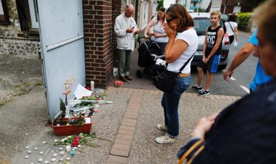 Een vrouw houdt enkele momenten van bezinning in acht voor het huis van de vermoorde priester Jacques Hamel.