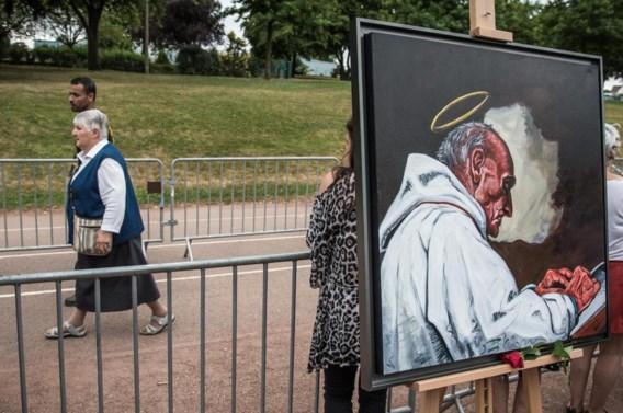 Zuster Danielle, zelf even gijzelares van de terroristen, wandelt voorbij het portret van de vermoorde priester Jacques Hamel.