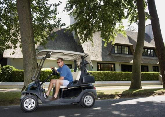 Een bezoeker van de Royal Zoute Golf Club rijdt met een golfwagentje door de lokale villawijk.