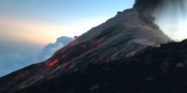 Wandelaars staan vlakbij krater bij vulkaanuitbarsting