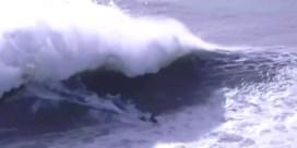 Surfer kruipt door het oog van de naald bij monstergolven in Portugal