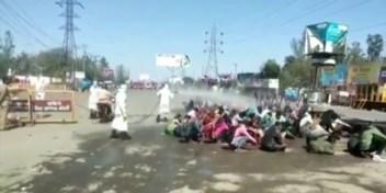 Migranten besproeid met desinfectant, duizenden wachten opeengepakt op een bus naar huis
