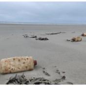 Na storm Odette: honderden flessen motorolie uit 1966 op stranden aangespoeld