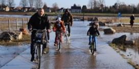 Oevers en fietspaden lopen onder water door hoog water in Maas