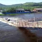 Houten brug en vrachtwagen meegesleurd door kolkende rivier in Rusland