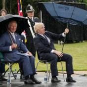 Boris Johnson worstelt naast prins Charles met paraplu